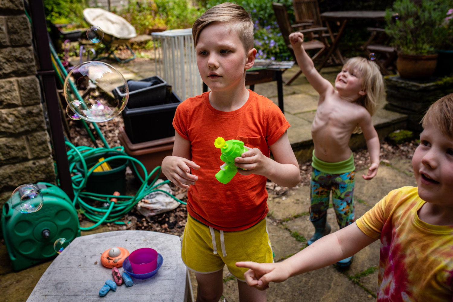 Three young brothers stand in their garden blowing and catching bubbles during this unposed family photo shoot  in Manchester, UK.