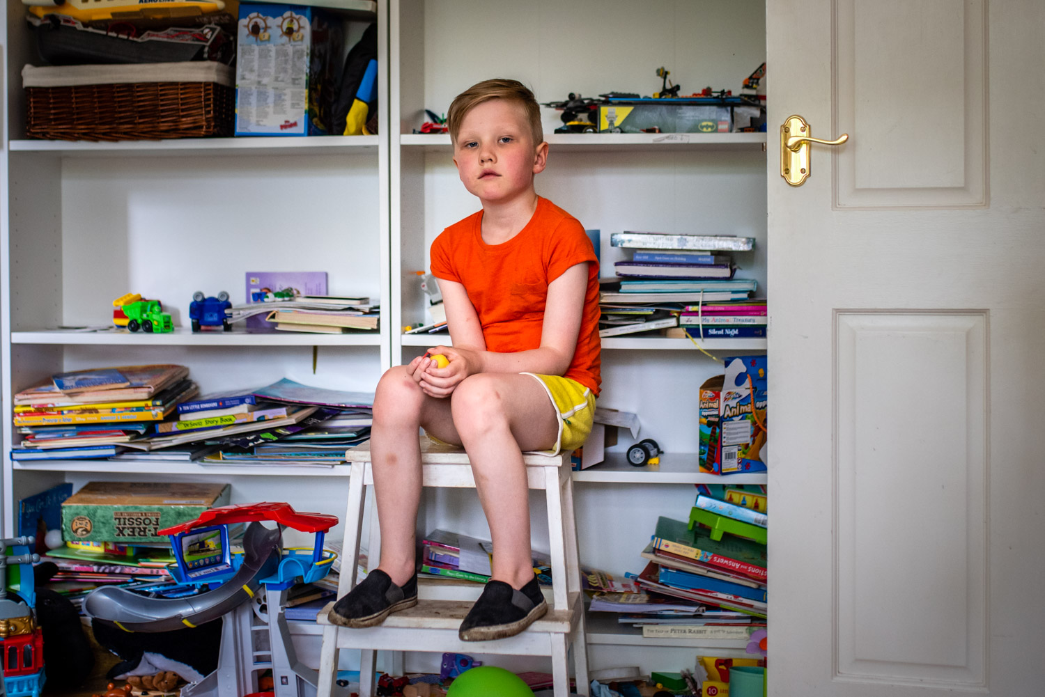 A portrait of a young boy sat on a stool in his play room surrounded by toys during this relaxed family photo shoot in Manchester, UK.