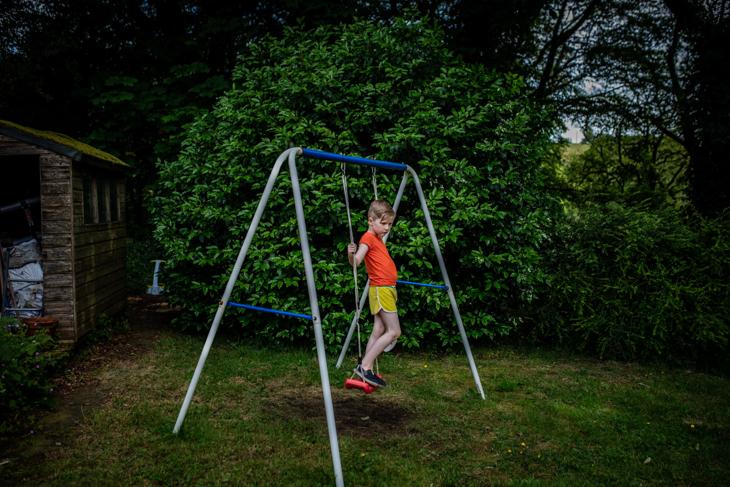 A portrait of a young boy standing on a swing in his garden, staring into the distance during this relaxed family portrait photo shoot in Manchester, UK.