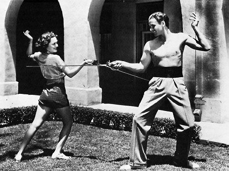 Oliva de Havilland and Errol Flynn practicing fencing