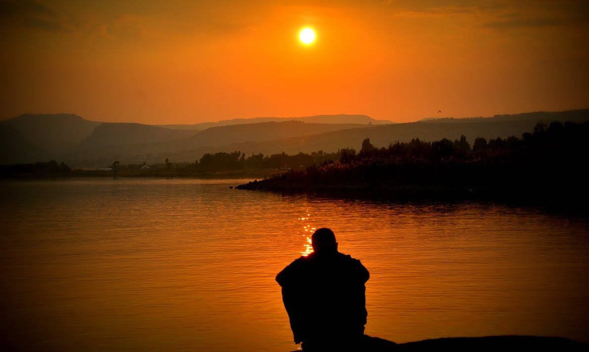 thumbnail of man sitting at edge of lake at sunset
