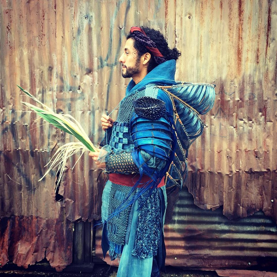 Igor Santizo as  Chronos  in a garment made from yucca, abaca (a species of banana), silk and dyed willow bark. He holds a sheaf of stripped yucca leaves. He is armed against the sun with expanding screens protecting the head and spine, sheathed leaf sleeves that shade and let breeze through.