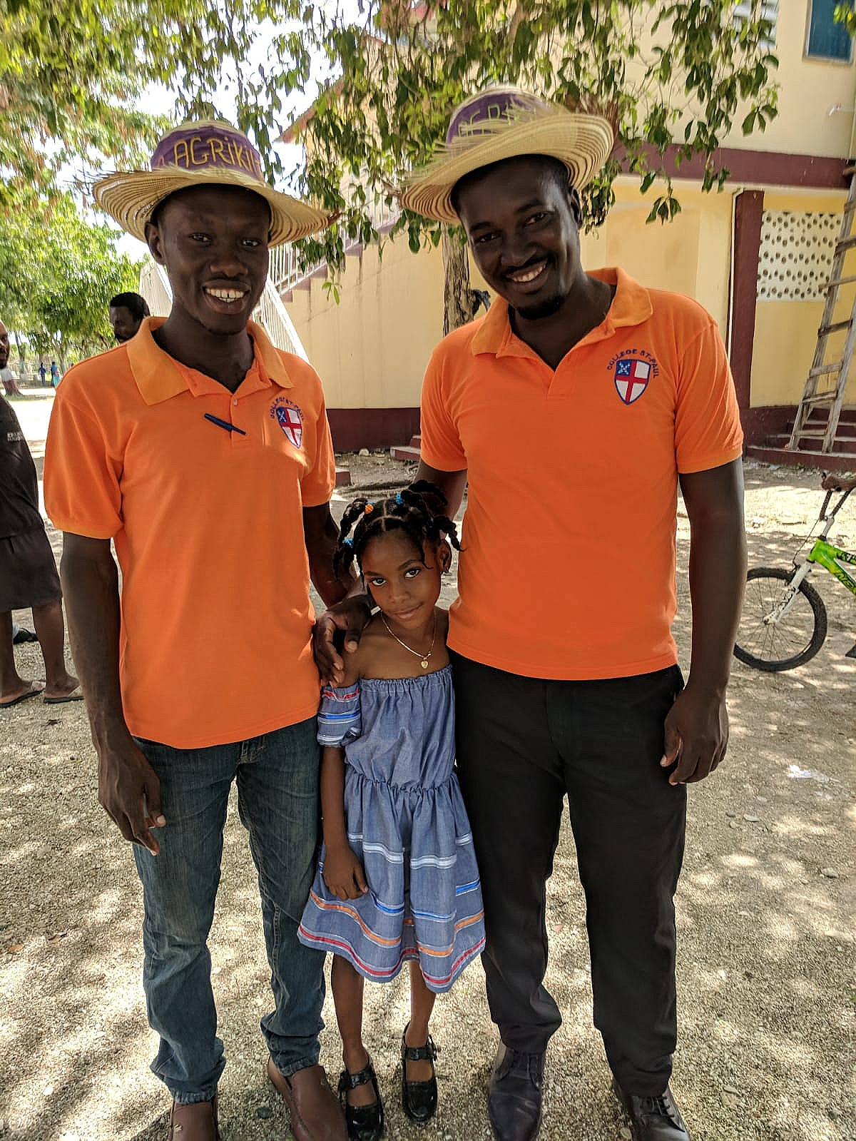Agronomist Raphael (right) stands with Vladimy (left) and a young Harvest Fest attendee. Raphael gave the keynote speech of the Harvest Fest, and Vladimy, the entrepreneurship teacher at Paul's School, emceed the event.