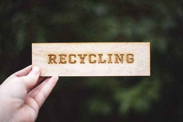 A small wood engraved sign for recycling