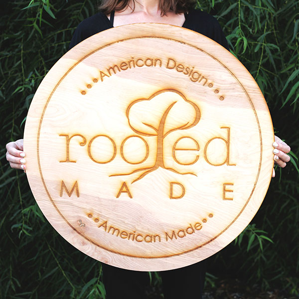 A hand crafted circle wood business sign, for hanging on the store wall.