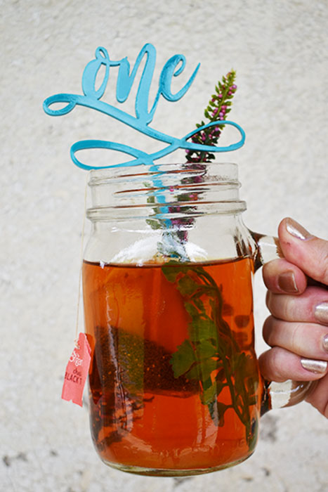 """A fun """"one"""" drink stirrer laser cut from turquoise acrylic for a baby first birthday party."""