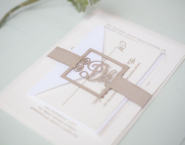 A custom laser cut monogram belly band we made to wrap around a wedding invitation.