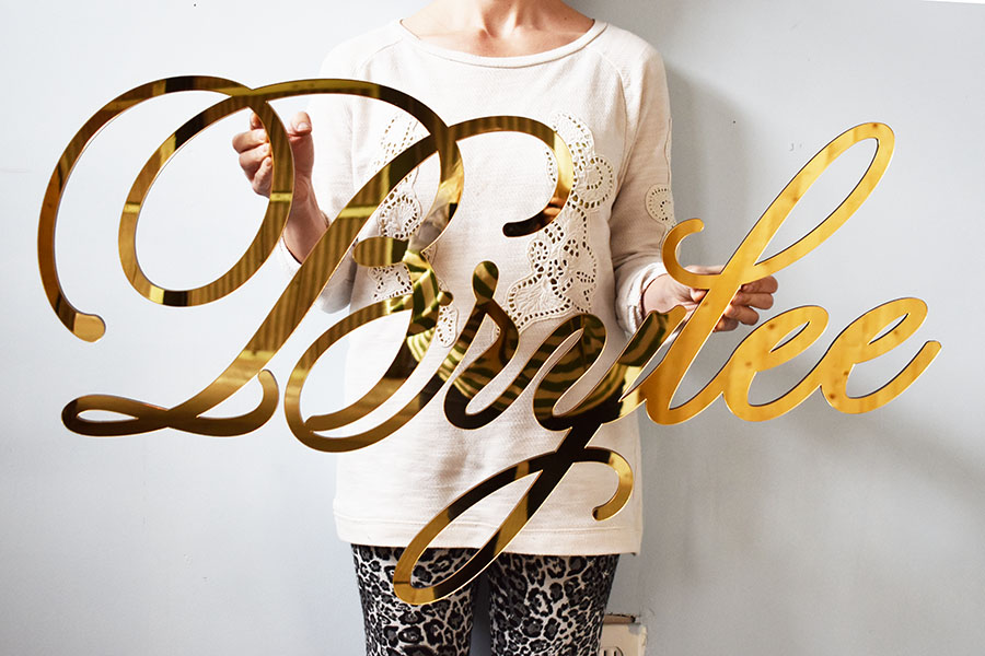 A gold mirror name sign using our custom font.