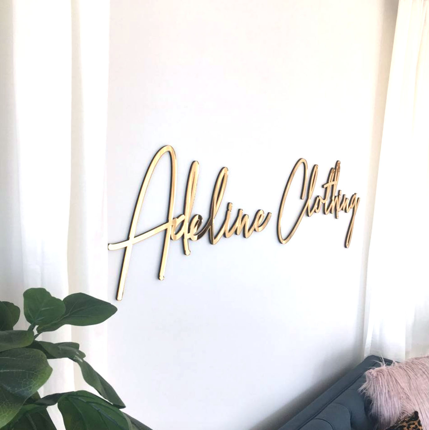 A 6 foot long mirrored business sign for a clothing company.