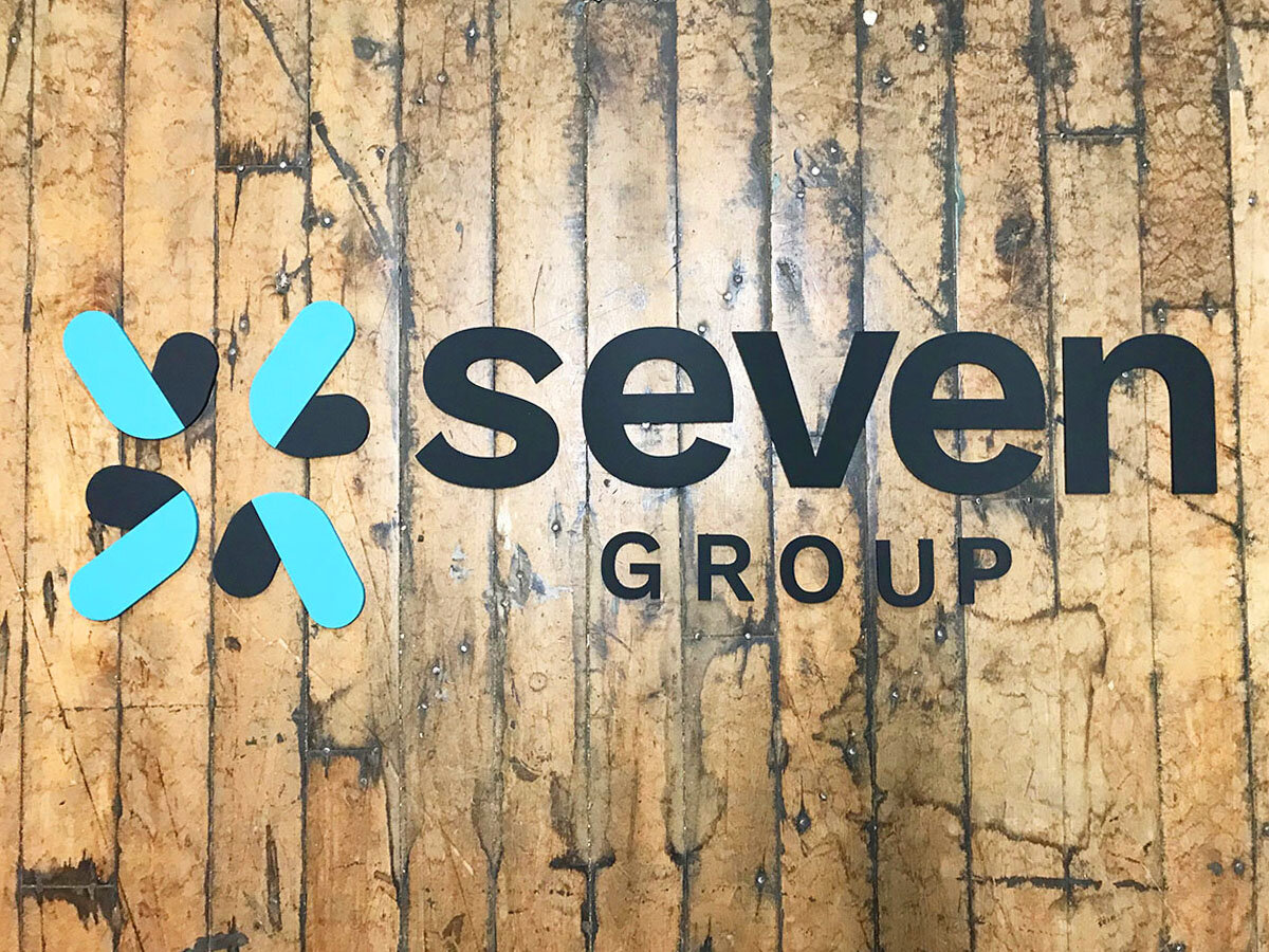 matte black acrylic and turquoise business logo sign we made for the Seven Group in NYC