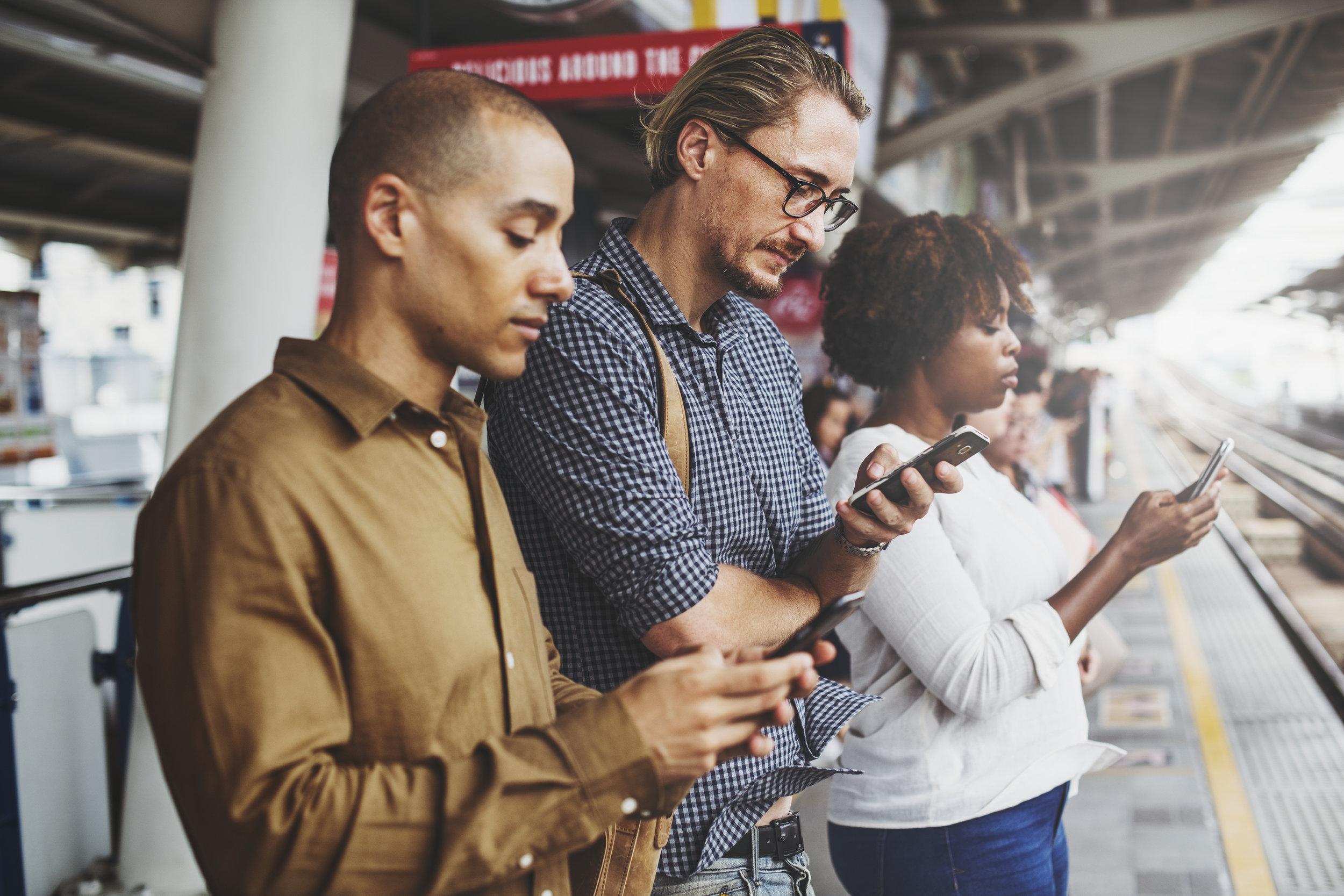 People using smartphones on the train platform