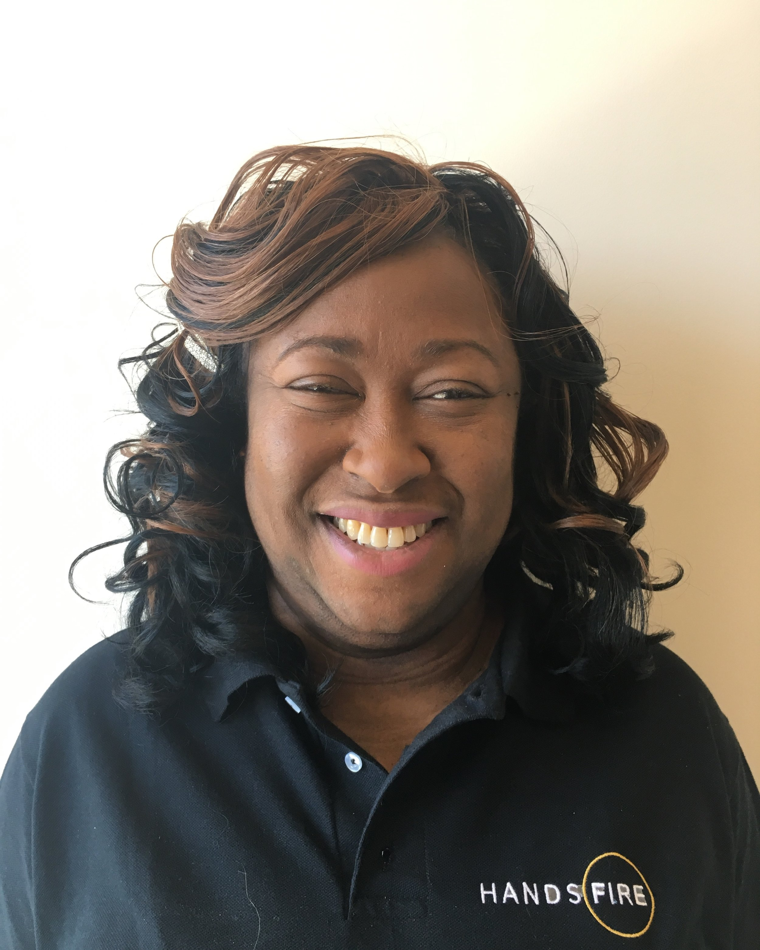 Photo Description: Alicia Modeste smiling wearing a black polo shirt with the Hands of Fire logo on the right hand side.