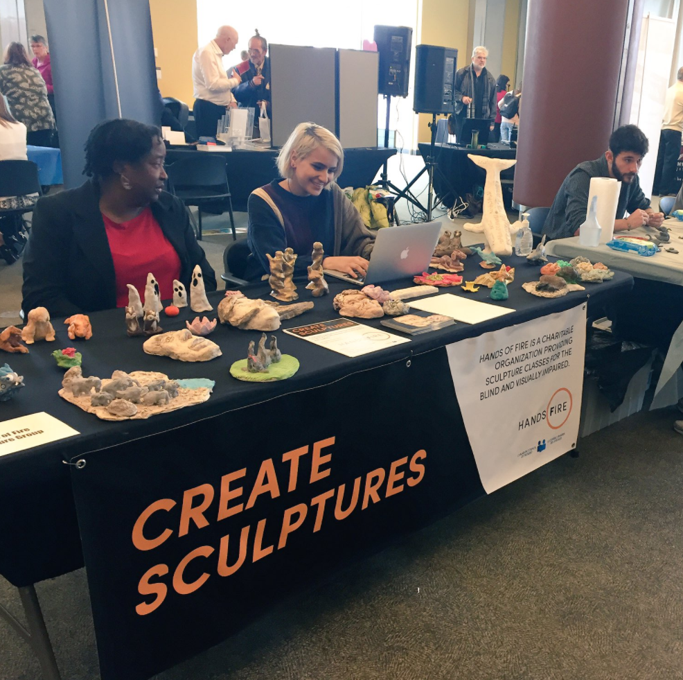 """Photo Description: Table with sculptures with a banner in front which reads """"Create Sculptures: Hands of Fire is a charitable organization providing sculpture classes for the blind and visually impaired community"""". From left to right three Hands of Fire staff are sitting there from left to right: Noora, Alicia, and Douglas."""