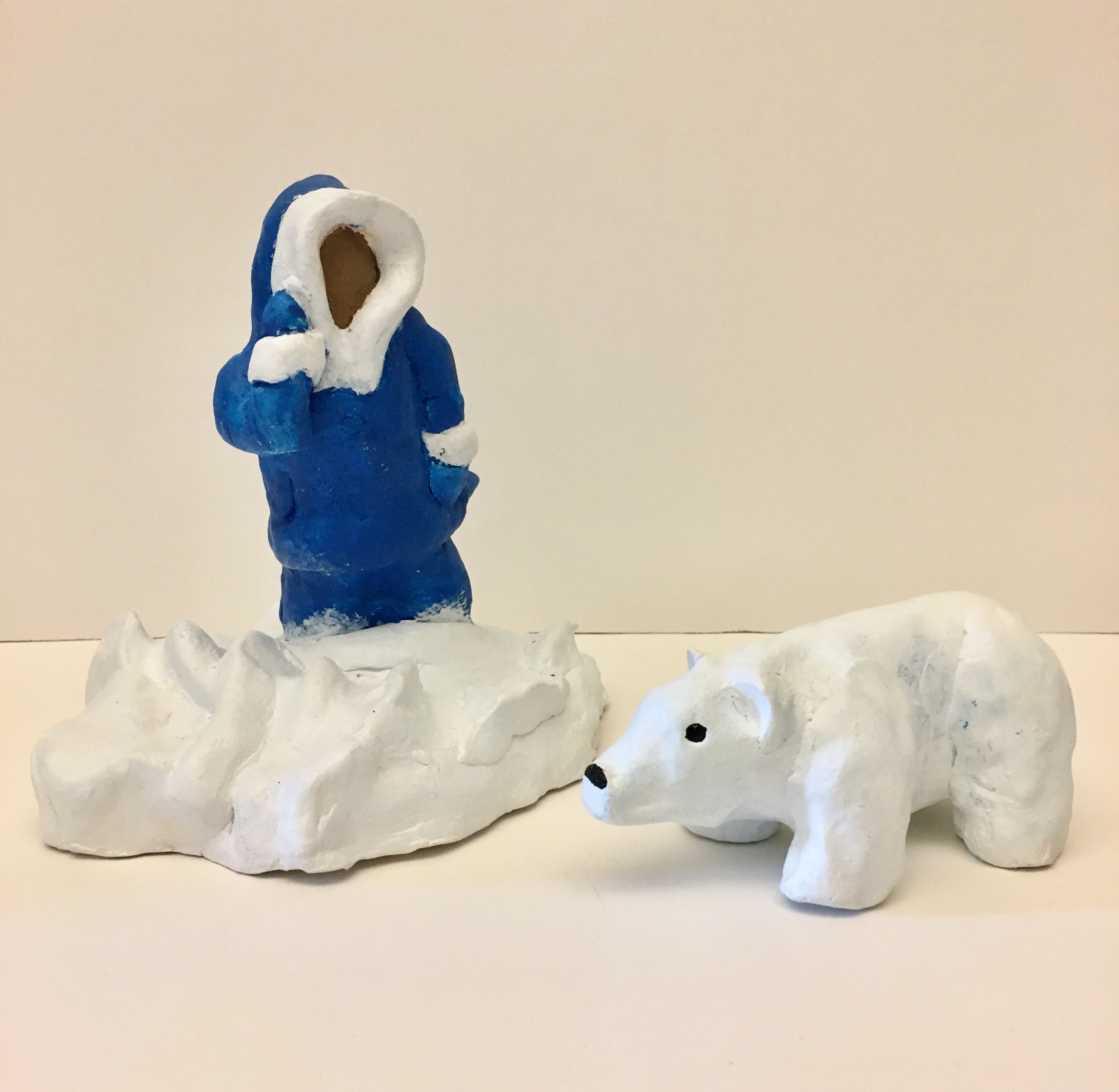 Photo Description: The sculpture depicts an Inuk standing to the left on a bed of snow in a blue parka with white fur trimming on the hood and sleeves; his left arm raised to his ear. To the right is a small white polar bear with black eyes and a black nose stairs forward.