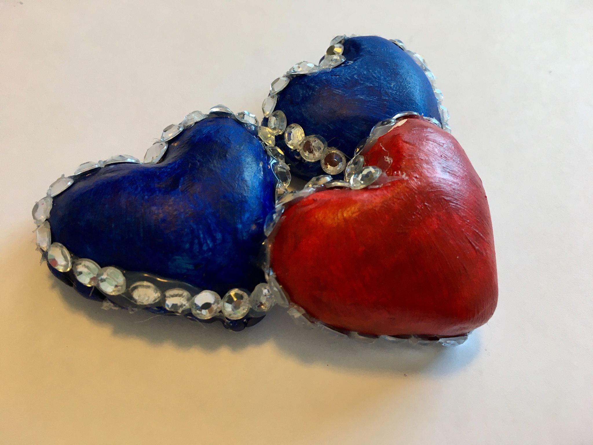 Photo Description: This sculpture depicts a red heart-shaped jewel resting in-between two blue heart-shaped jewels. All three are trimmed with silver gems.