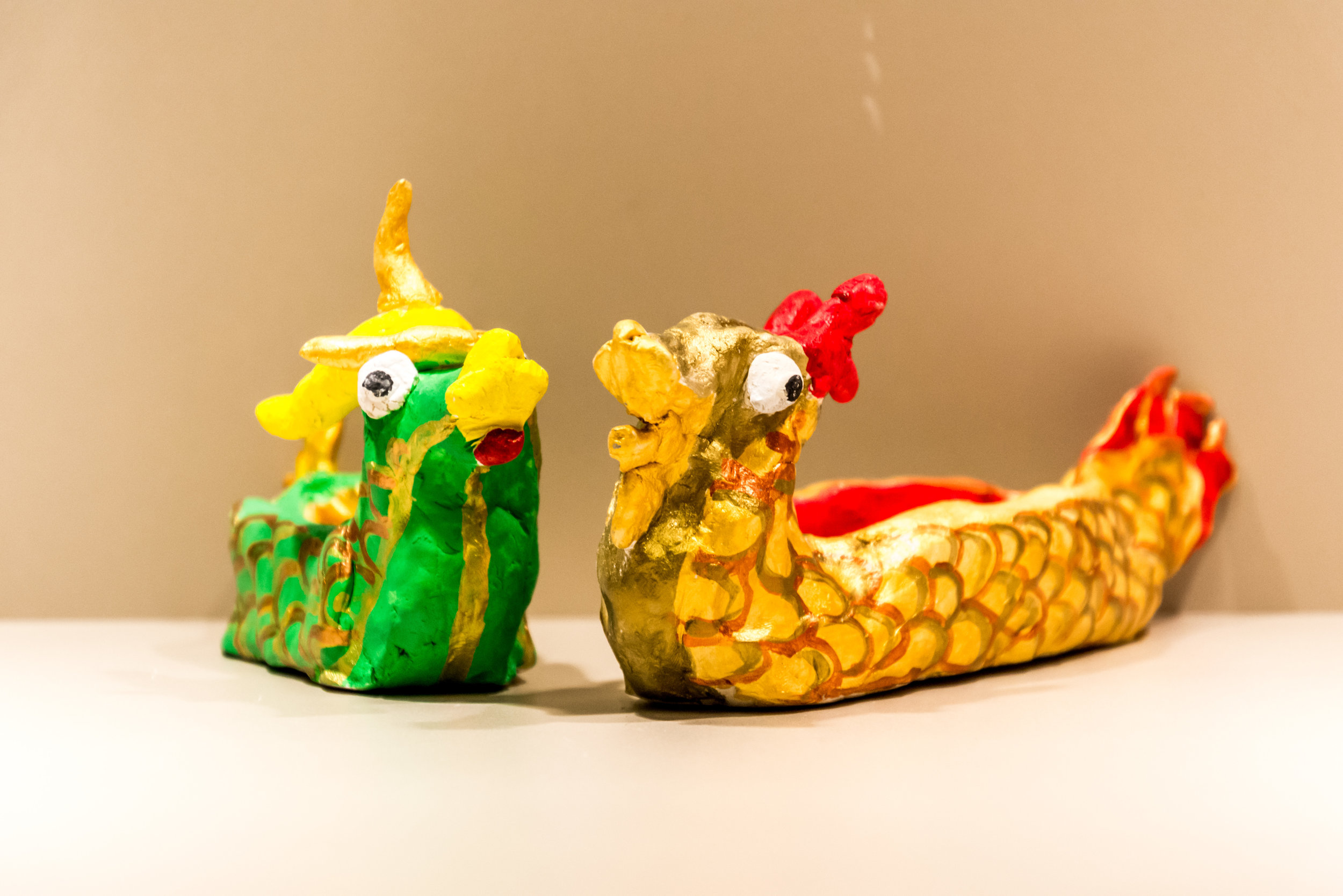 Photo Description: Two dragon boats with a green on with gold trimming one the left and a gold with red trimming one on the right.