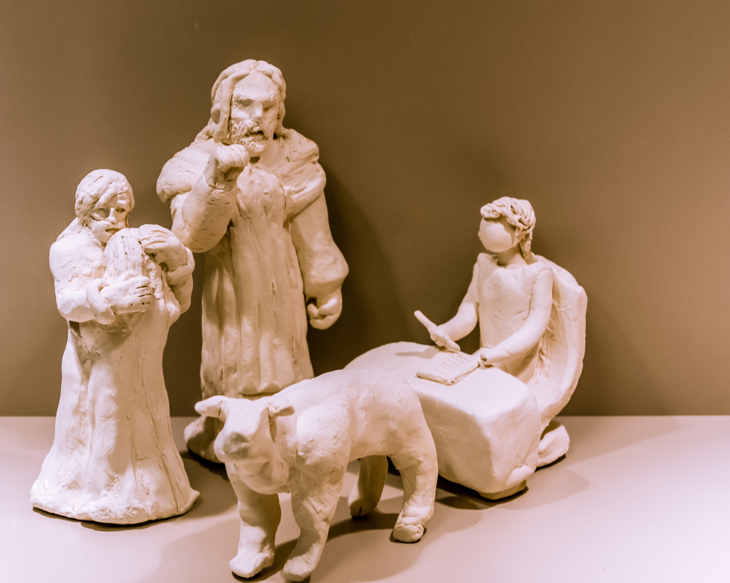 Photo Description: Four white sculptures from left to right they are one of a Christ holding an woman; Christ with his hand in a knocking position; a bull looking upwards; and a woman seated at a table with a pen in her hand.
