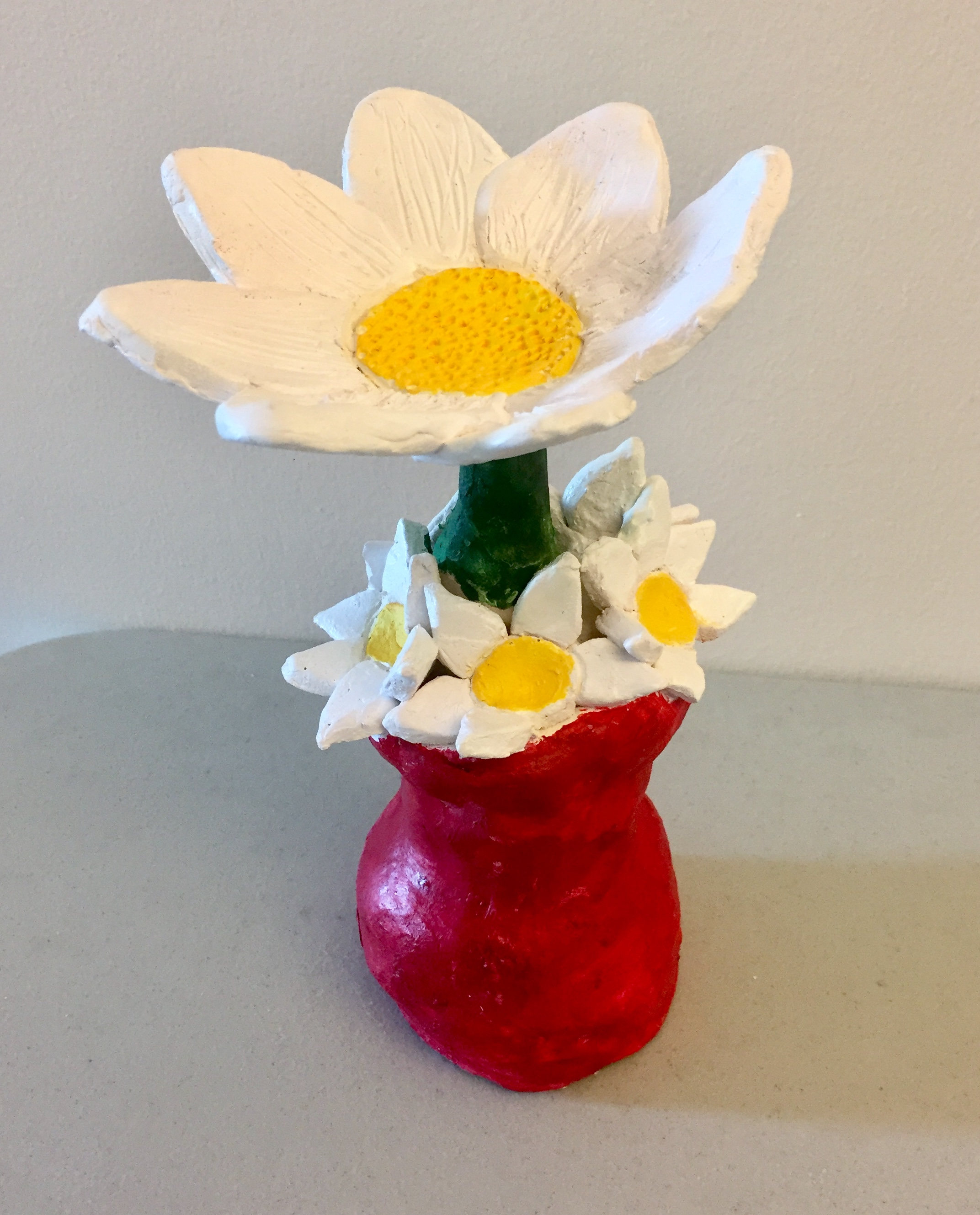 Photo Description: Sculpture of a large white daisy with a with a green stem in a red vase with four smaller daises resting on the lips of the vase.