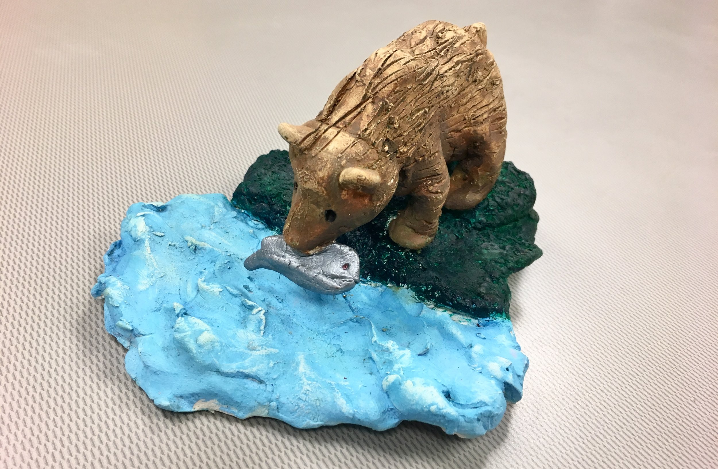 Photo Description: Sculpture of a light brown bear with a fish in its mouth standing on dark green grass with rough blue water.