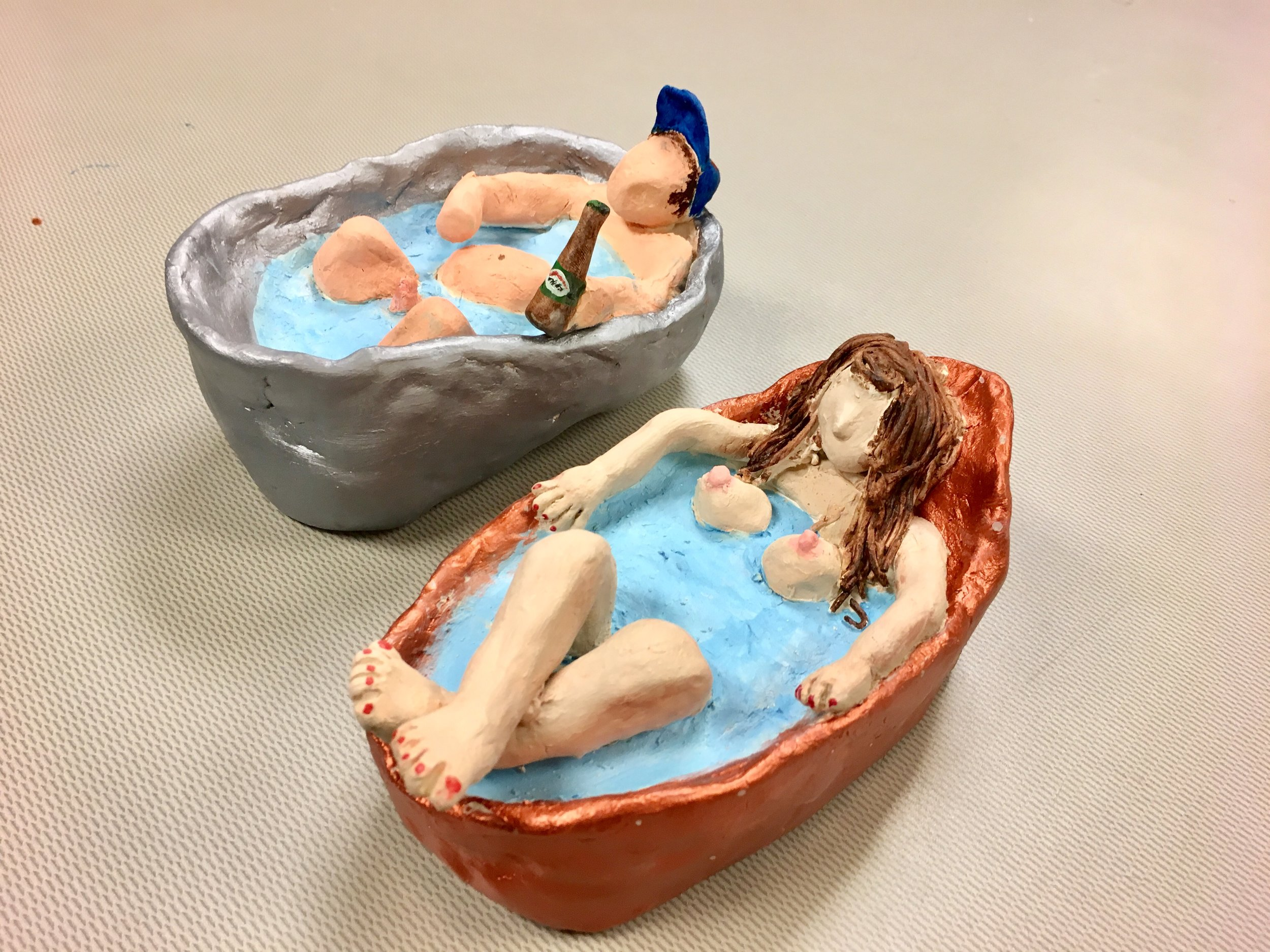 Photo Description: To the left is a sculpture of a naked man in a silver bath with his knees bent out of the water and his stomach and penis protruding from the water as he holds a beer and wears a blue cap. To the right is sculpture of naked woman in a rose gold bath with her legs crossed on the edge of the bath with her breasts protruding out of the water.