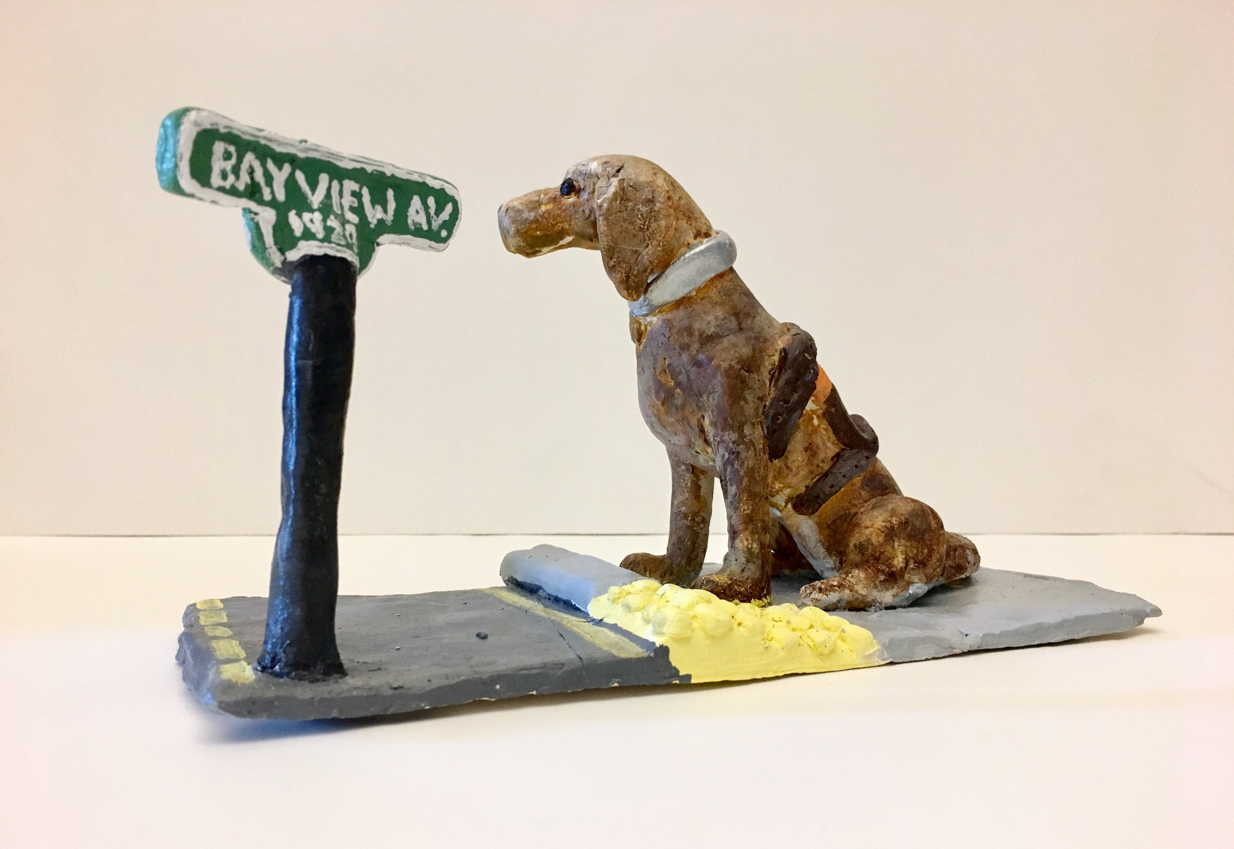 "Photo Description: This sculpture depicts a golden lab guide dog standing on grey asphalt at an intersection looking forward. To his left a street sign reads ""1929 Bayview Av.""."