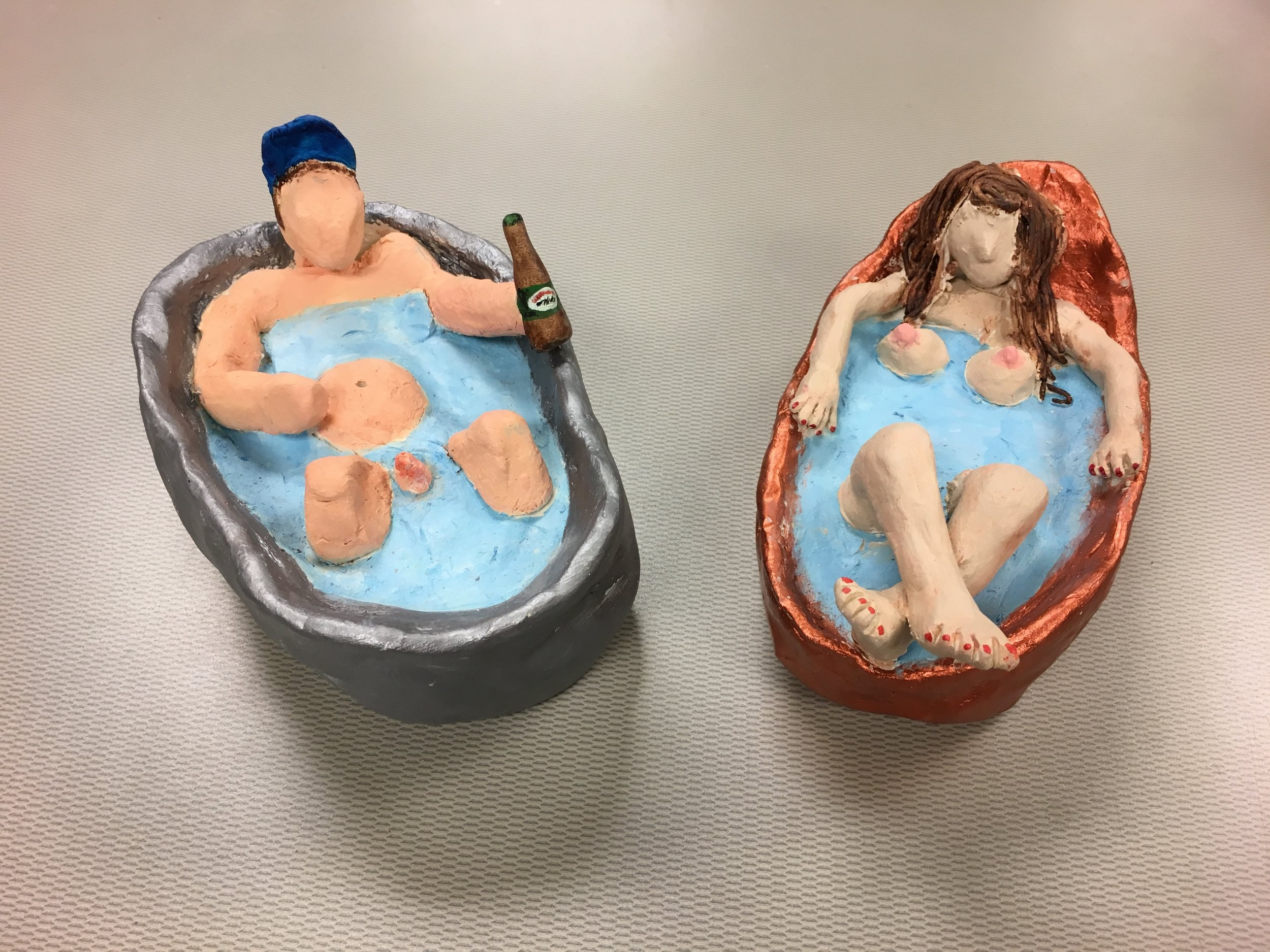 Photo Description: Two bathtubs side by side at an inwards angle. On the left side is a man in silver bathtub a beer and wearing a blue jays cap; on the right is a woman in a rose gold tub with her legs crossed.