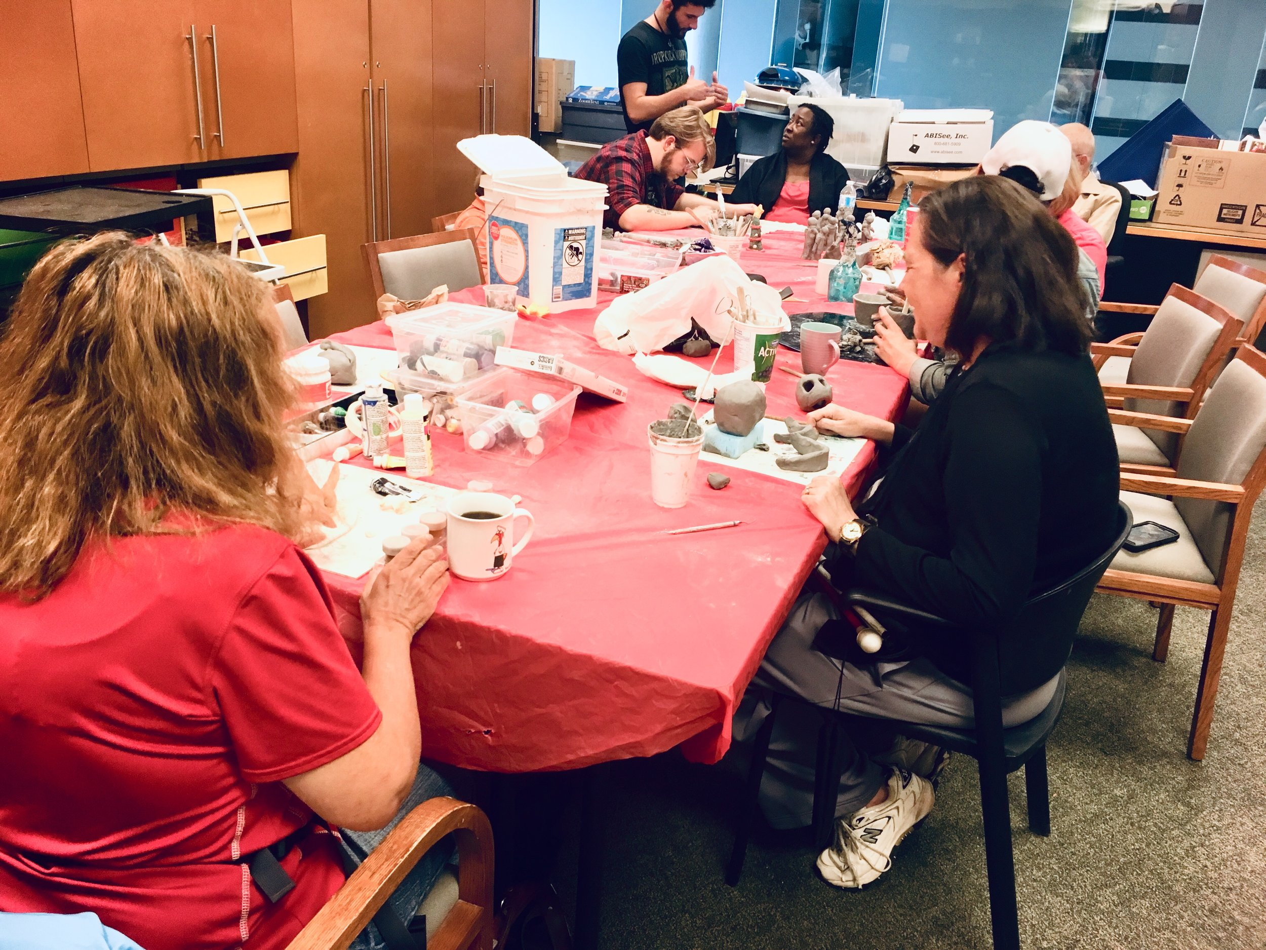 Photo Description: Members seated at a long rectangular tables with a red table clothes and clay on the table; seven individuals are seated at the table and one individual on the far left corner is standing speaking to chapter president, Alicia Modeste.