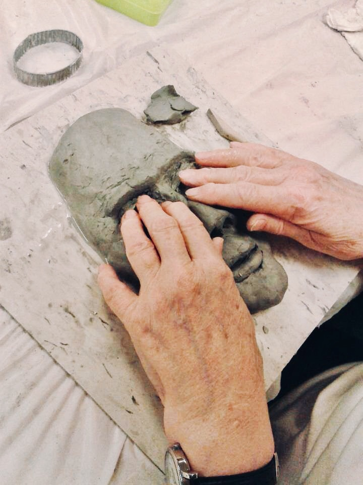 Photo Description: Two hands resting on the eye sockets of a semi-formed sculpture of a face in grey clay.