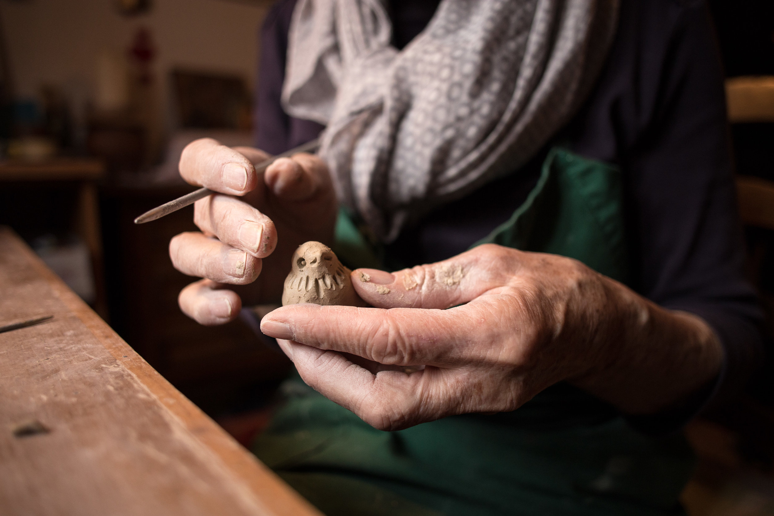 Photo description: Sculptor holding a metal pointed tool in their left hand and a sculpture of a bird in their left hand.