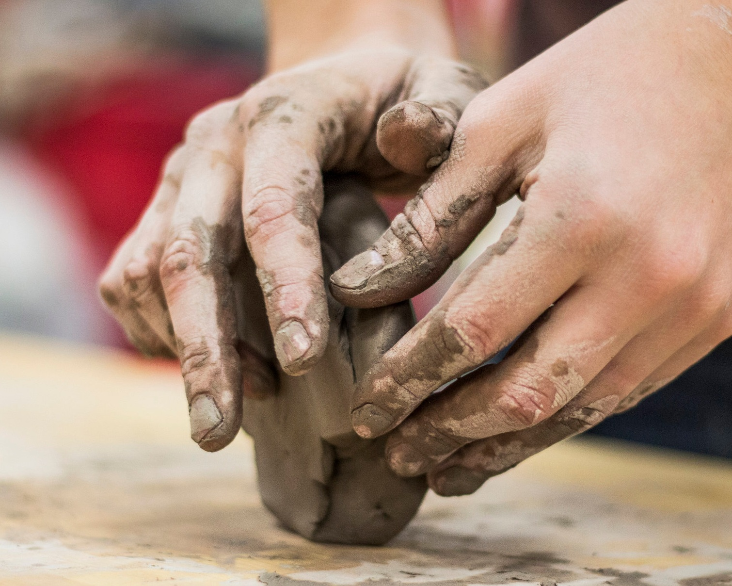 Photo Description: Two hands holding a rectangular piece of grey clay.
