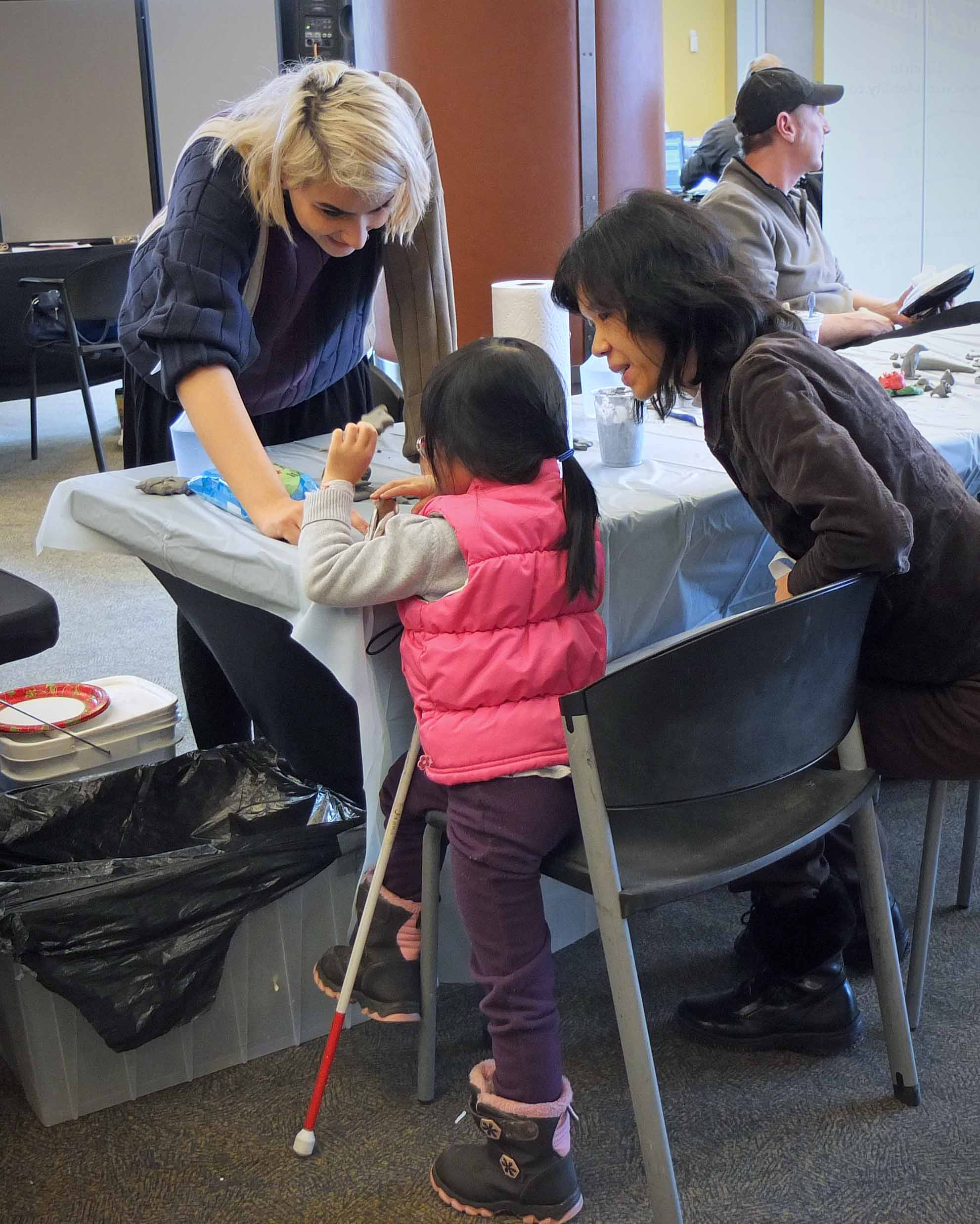 Photo Description: Noora standing behind a table with a grey table cloth teaching a young child wearing a pink vest and holding a cane with her mother seated to the right of her.