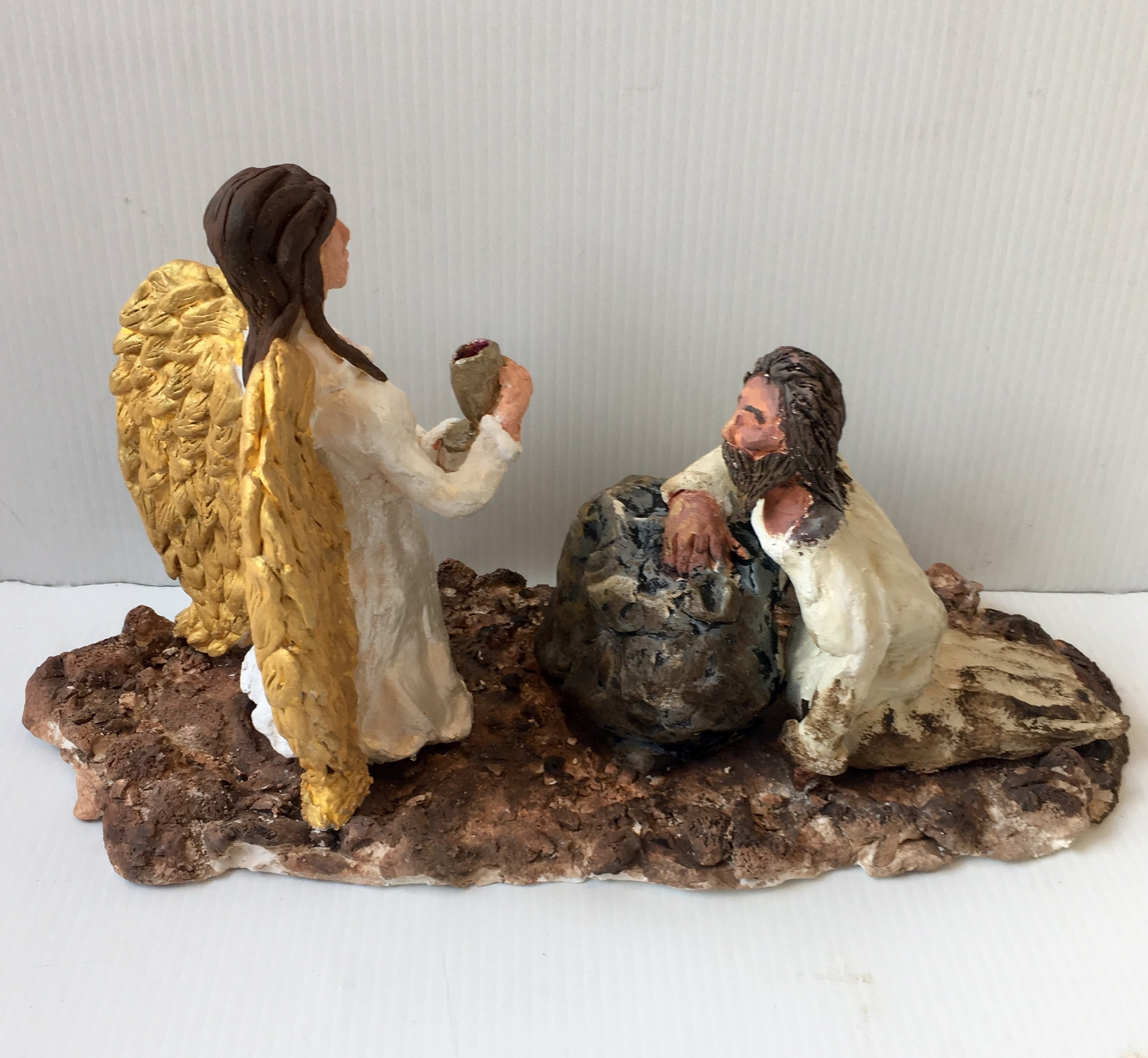 Photo Description: Christ kneeling on a rock with his white robes covered in dirt looking upwards towards and angel standing gazing Christ in the eyes with a golden chalice in hand.