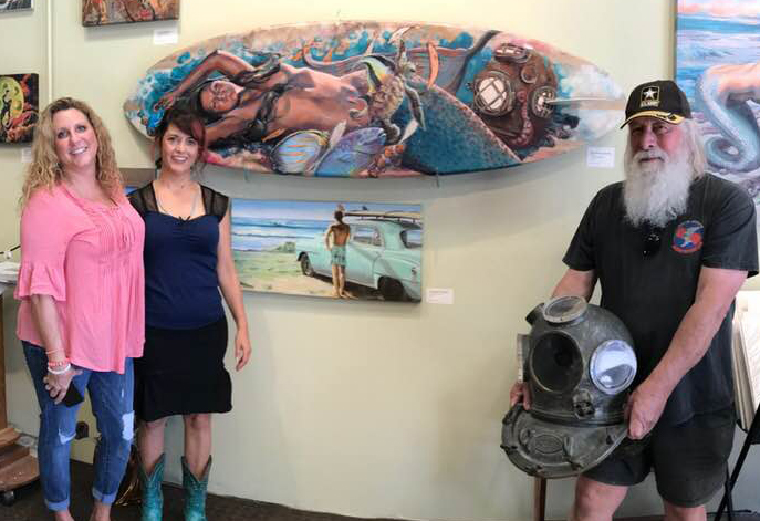 """This warm water surfer is taking home the mermaid surfboard, """"Warm Water, Warm Heart."""" Steve showed up with his phenomenal Kirby diving helmet."""