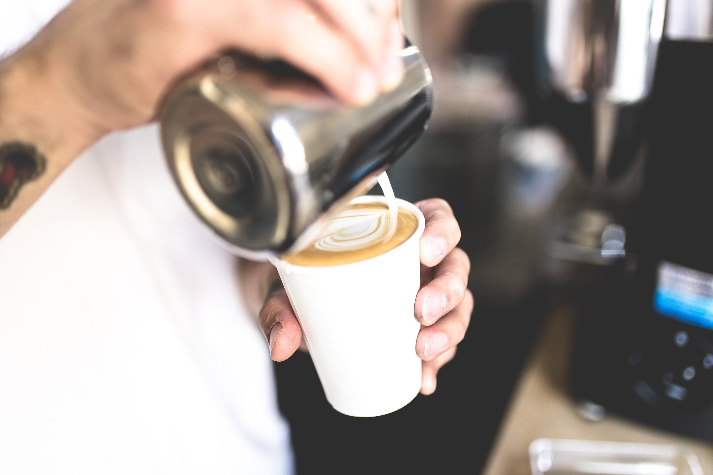 A barista pouring latte art into a to go cup