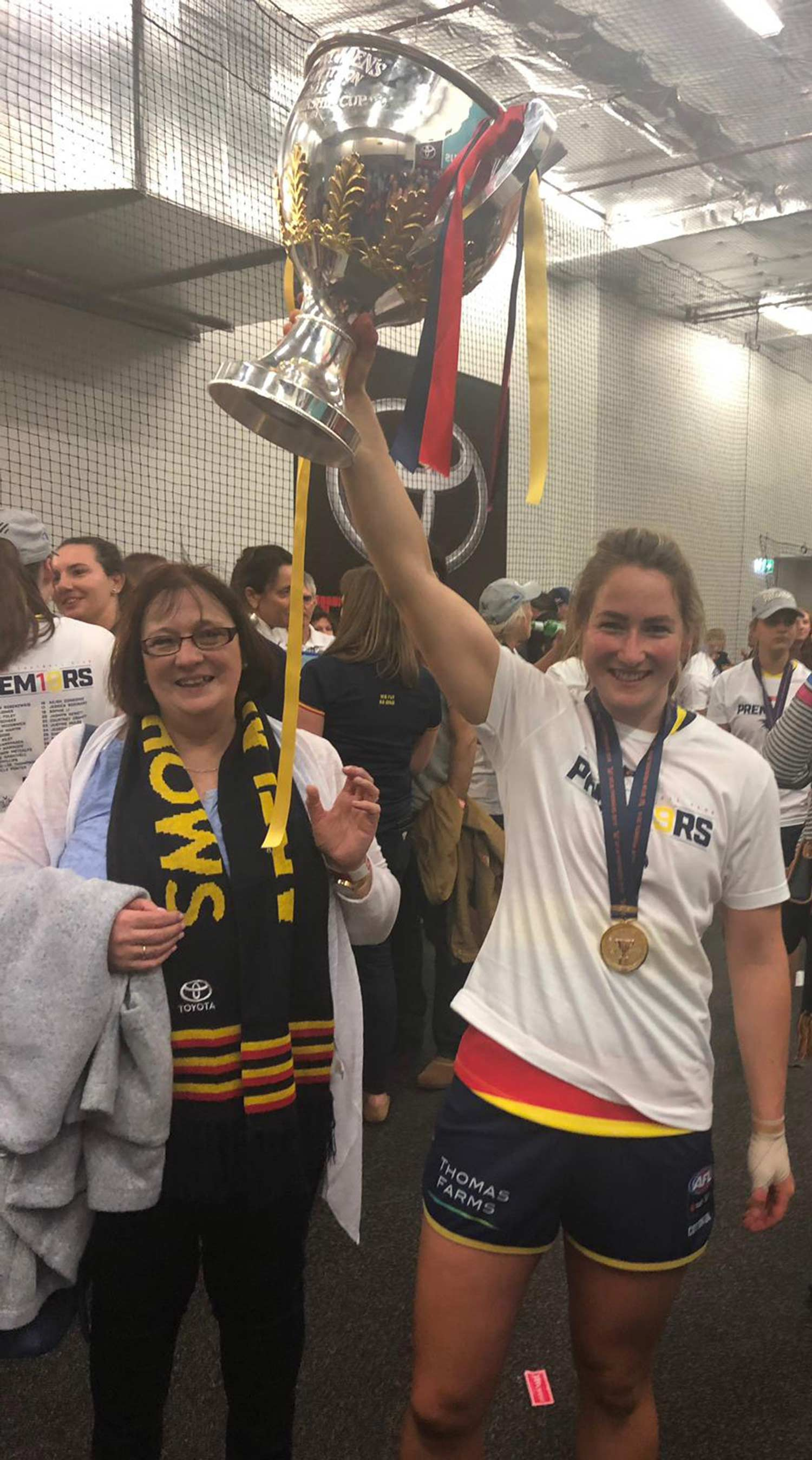 Ailish Considine of the Adelaide Crows with the AFLW Premiership Cup alongside proud mum Kay.