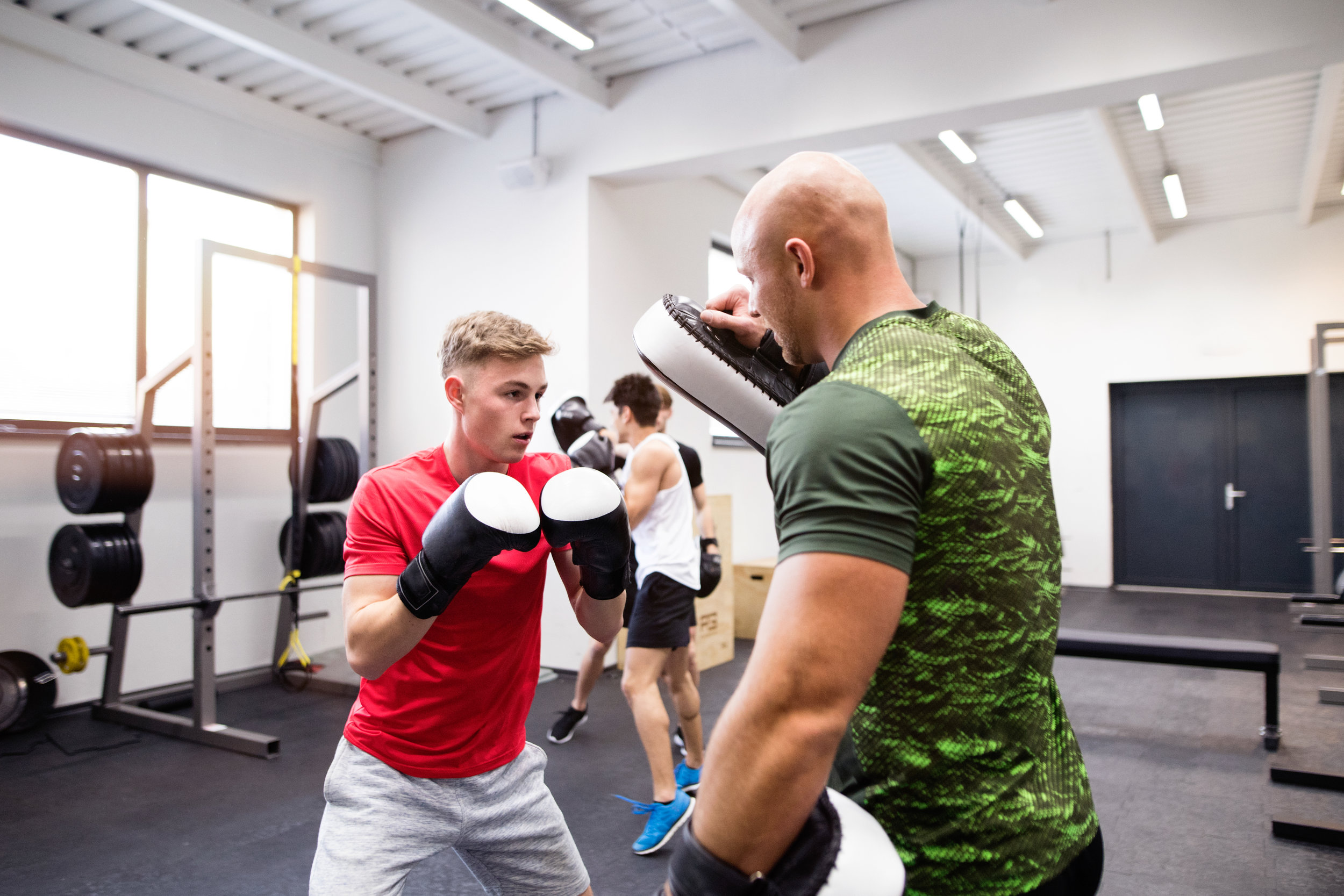 graphicstock-handsome-fit-young-man-boxing-with-his-personal-trainer-athlete-boxers-wearing-boxing-gloves-sparred-in-boxing-gym_SueZlZqLMb.jpeg