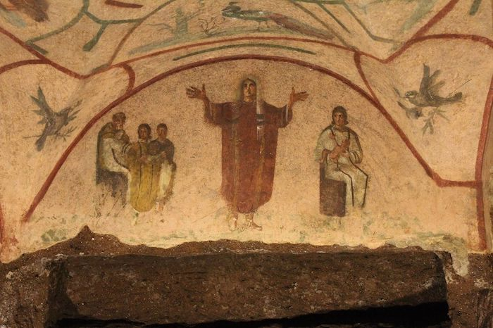 Woman holding hands in  orans  position, flanked with doves holding olive branches, and with peacock above. Fresco in the Catacombs of St Priscilla. 3rd century.