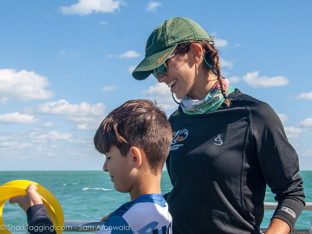 Showing a student how to reel in a line during a  Shark Tagging  expedition.
