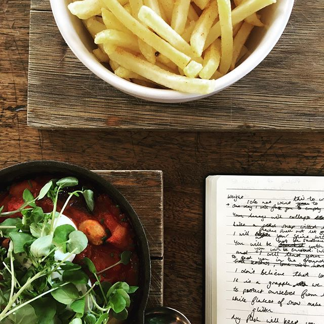 A lunch date with my notebook was long, long overdue. I'm running behind on #maymyselfandi after a busy and unusual week so it's been a nice change to just sit still and write. I'm currently deciding whether it would be weird to ask them to box up the fries so I can finish them later... waste not, want not. #poet #writing #amwriting #poetry #lunch #shakshuka #fries