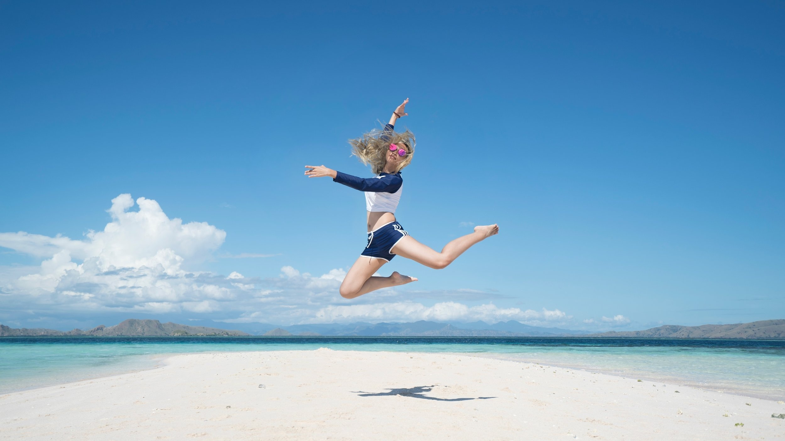 Rosie jumping for joy after saving £1,300 for her holiday in the Caribbean.