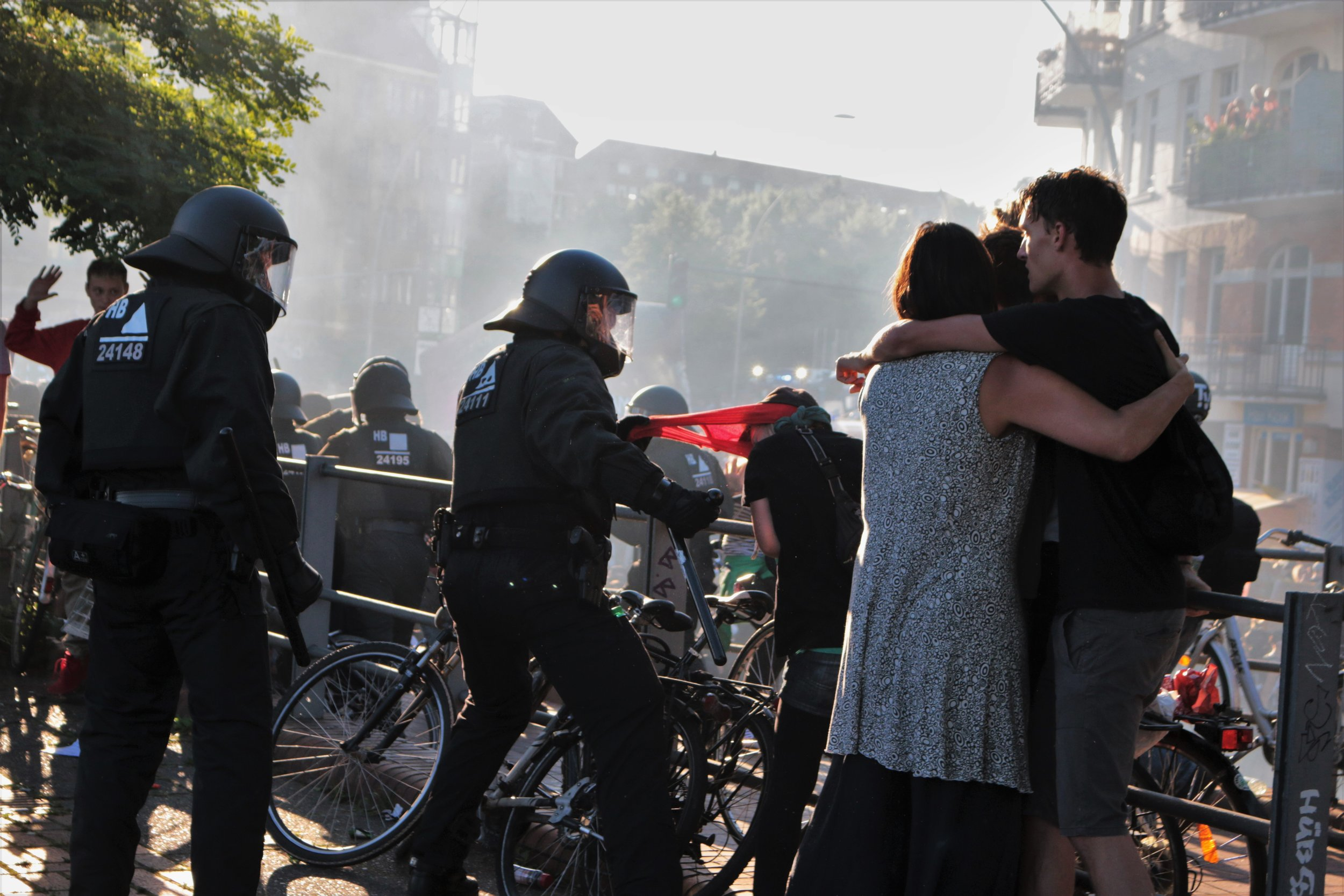 A police officer rips a mask off a protesters face. Police were later criticised for their heavy handed tactics