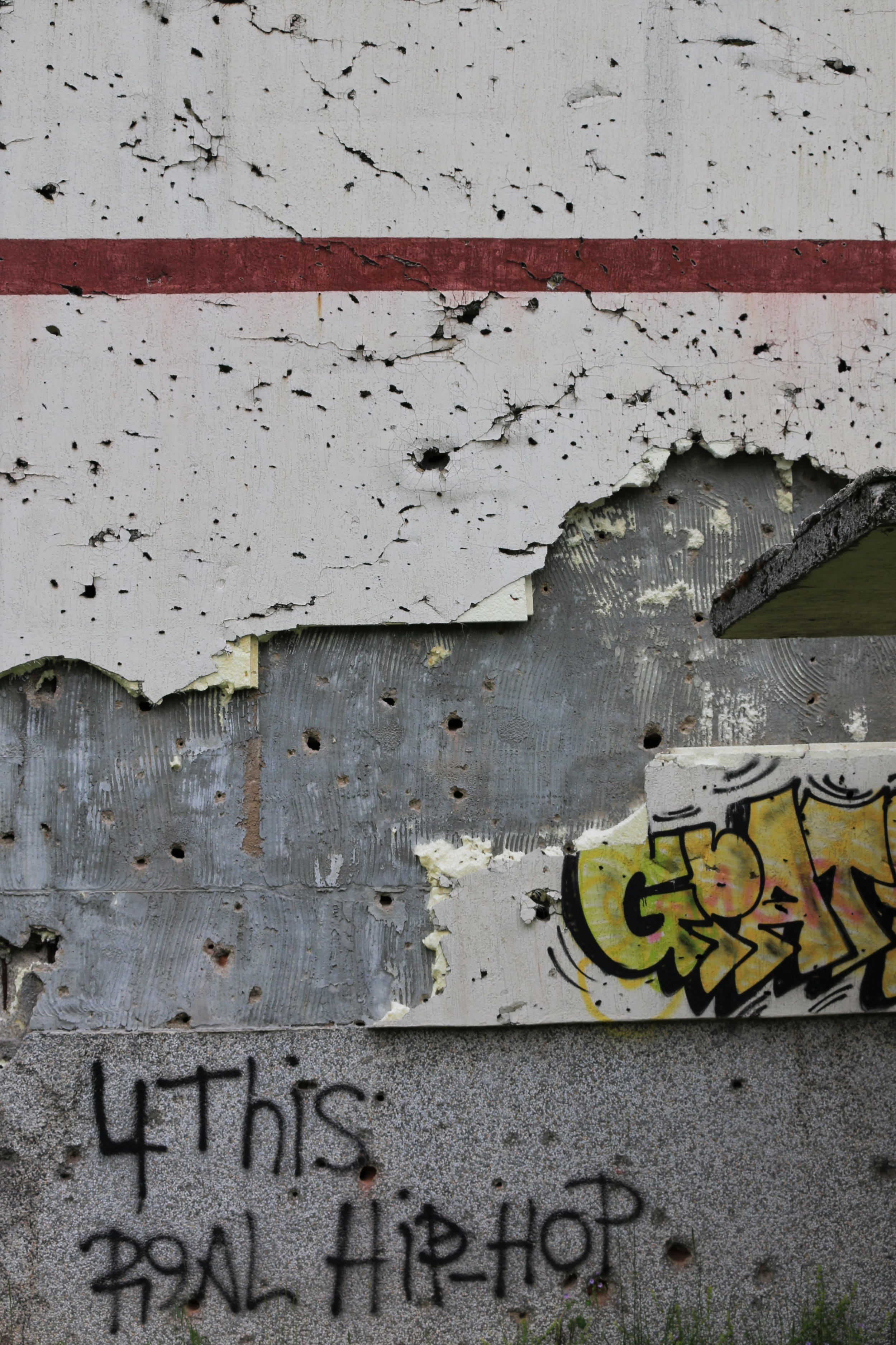 Graffiti covers a destroyed building in the hills that surround Sarajevo. The extent of the fighting seen in this area is evident by the bullet holes on the wall.