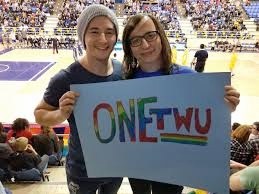 Morgane Oger poses at a TWU volleyball match with a OneTWU advocate