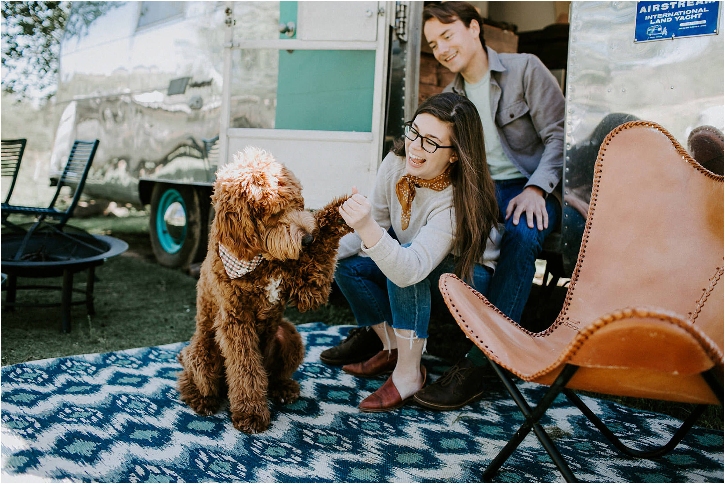 Couple sitting in airstream trailer with golden doodle dog.