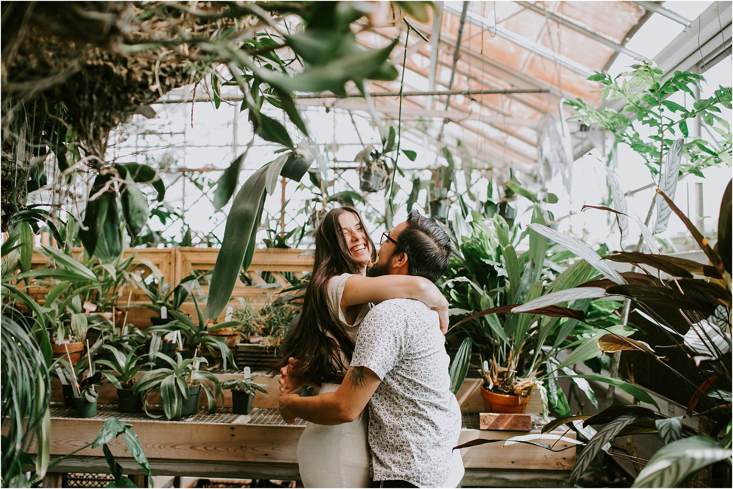 A couple is in a greenhouse surrounded by plants. They are embracing in a hug and she is laughing.