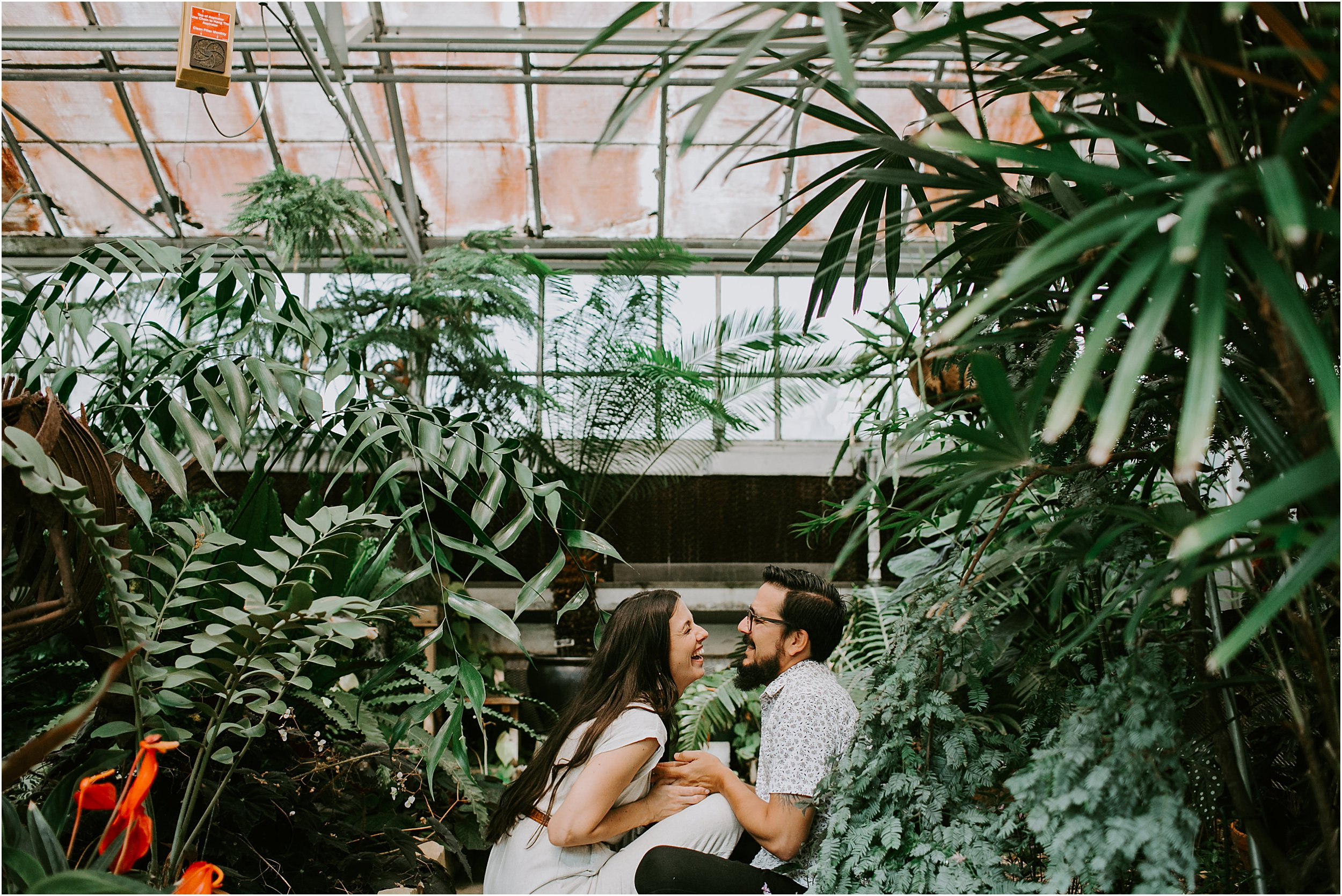 A couple is sitting on the ground in a greenhouse, facing each other. They are holding hands and the girl is laughing. There are tall green plants and a red flower.