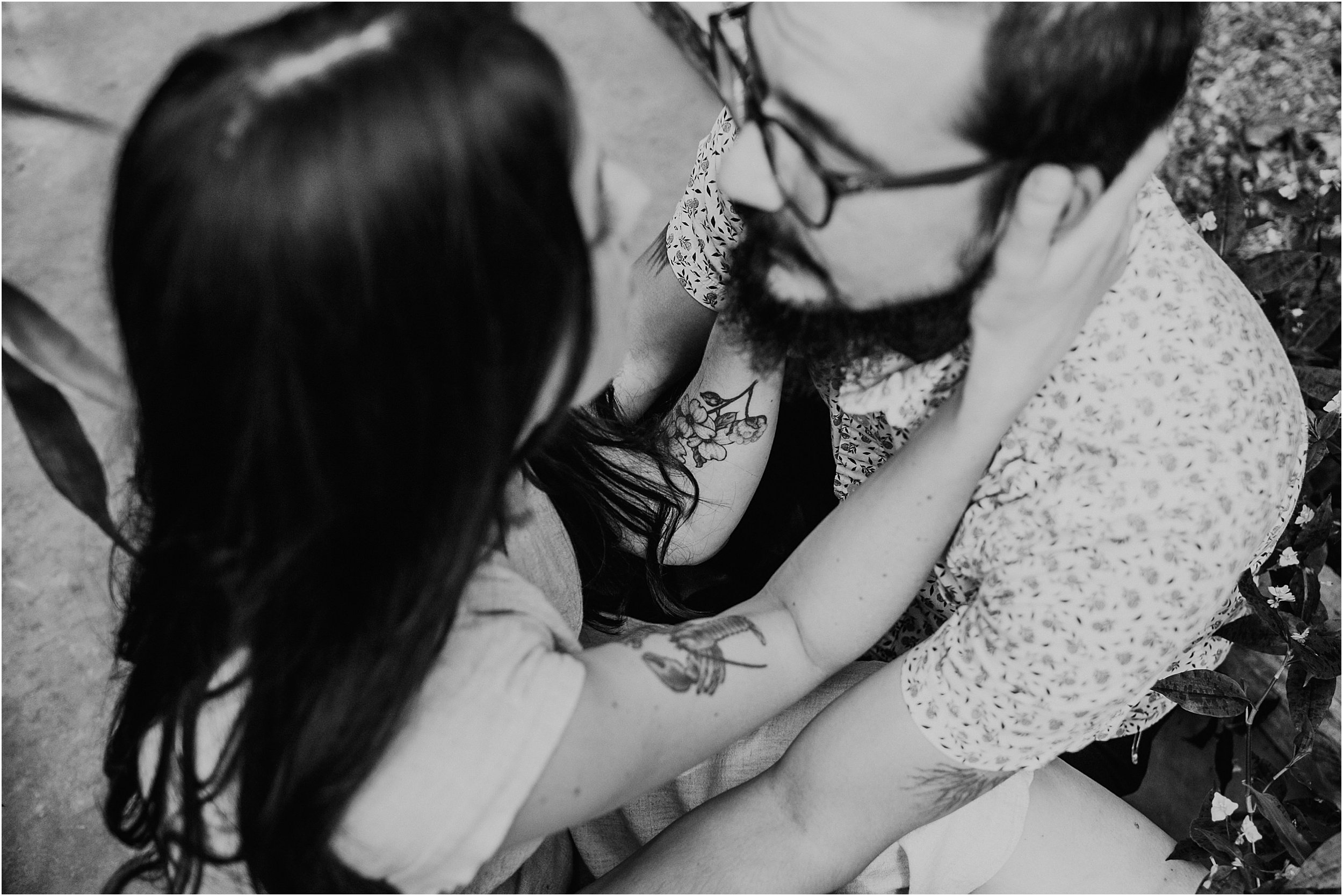 A couple is sitting on the ground, facing each other . The girls hand is on his cheek and they have tattoos on their arms. The image is black and white.