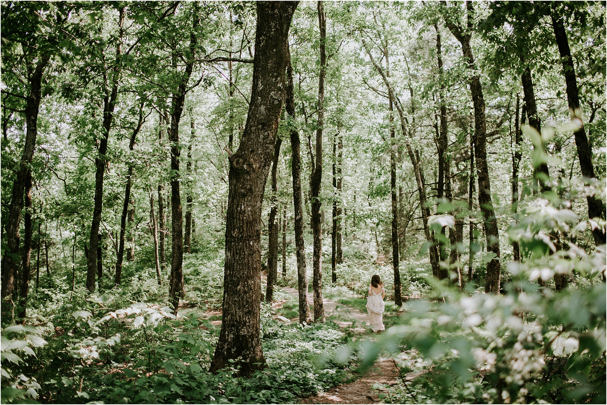 A woman in a wedding dress walk through the woods. It is dense with green leaves and she is wandering down the path.