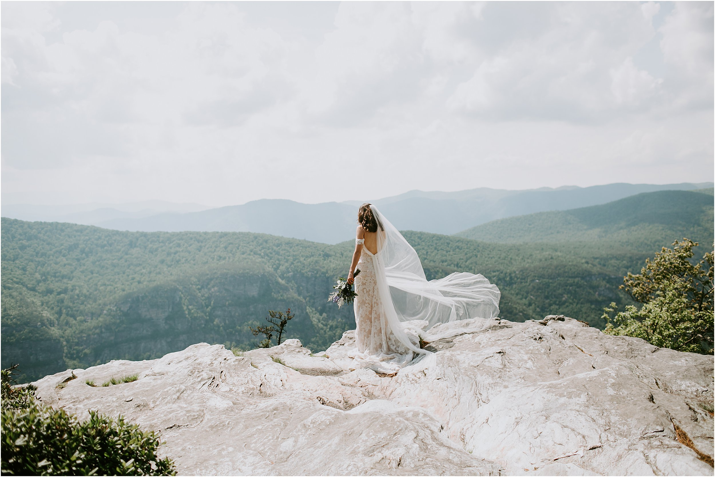 A bride in a wedding dress stands on a rock overlooking a valley. She is in the mountains of the Blue Ridge Parkway and her veil is blowing in the wind. She is facing away from the camera, looking at the mountains, and has a bouquet of flowers in her hand.