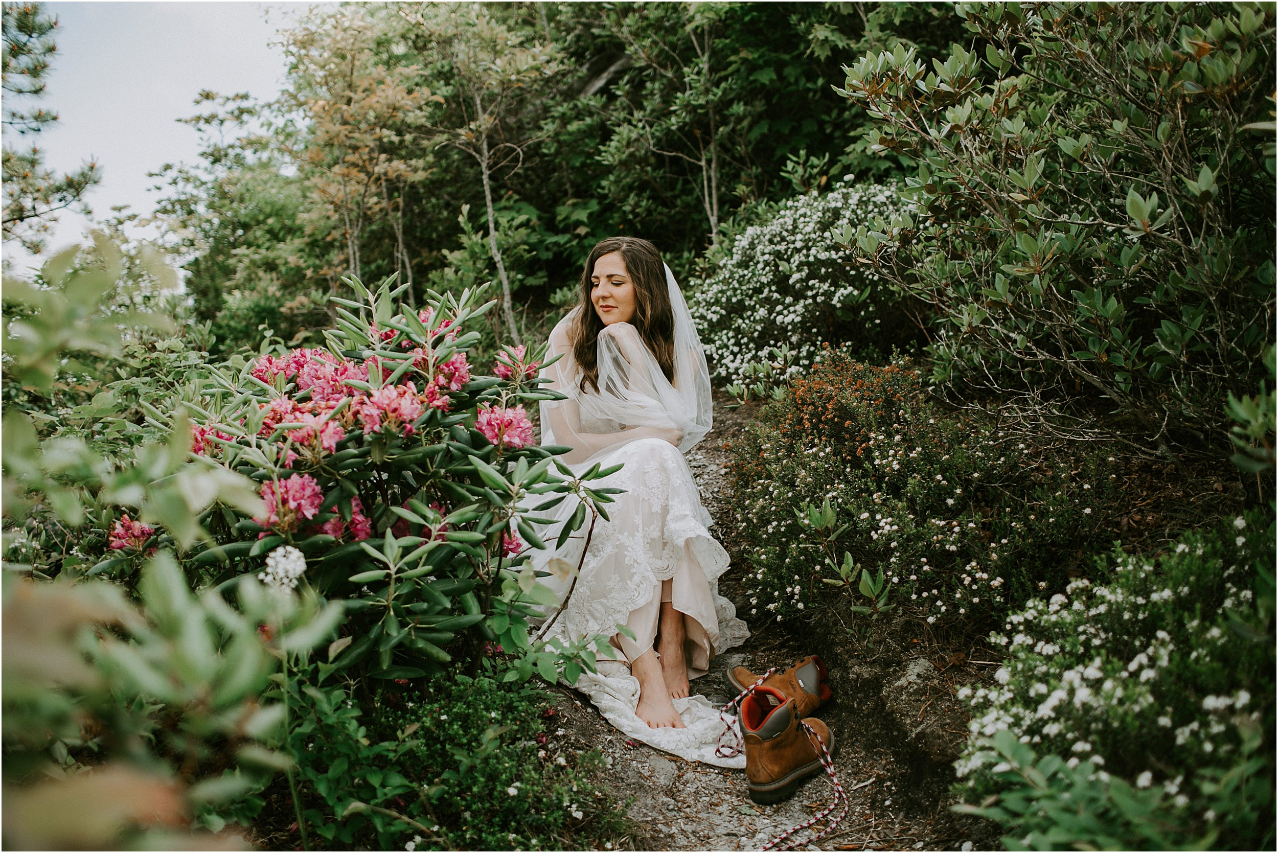 A woman in a wedding dress sits on a trail through bushes and pink flowers. She is barefoot and her hiking boots are off, she is resting.